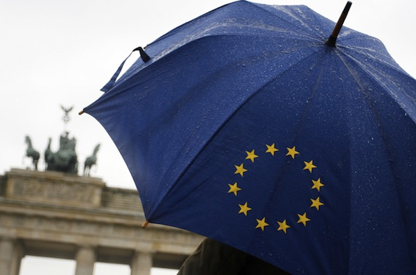 A woman with an umbrella depicting the logo of the European Union walks past Berlin's landmark, the Brandenburg Gate, 22 March 2007. The German capital is preparing for a meeting to take place 24 and 25 March of European heads of state to mark the 50th anniversary of the signature of the Treaty of Rome which established the European Economic Community, the fore-runner of the EU.    AFP PHOTO    DDP/CLEMENS BILAN    GERMANY OUT (Photo credit should read CLEMENS BILAN/AFP/Getty Images)