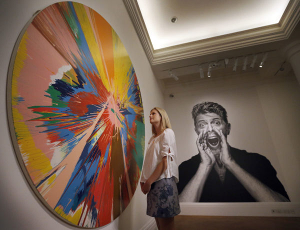 "A woman looks at a painting by Damien Hirst in front of a portrait of David Bowie at Sotheby's in London, Wednesday, July 20, 2016. Sotheby's employees lift the painting ""Air Power"" by Jean-Michel Basquiat at Sotheby's in London, Wednesday, July 20, 2016. More than 200 pieces from David Bowie's personal art collection went on public display for the first time with important paintings by 20th-century masters including Hirst, Jean-Michel Basquiat and Frank Auerbach before being sold at Sotheby's in November. (AP Photo/Frank Augstein)"